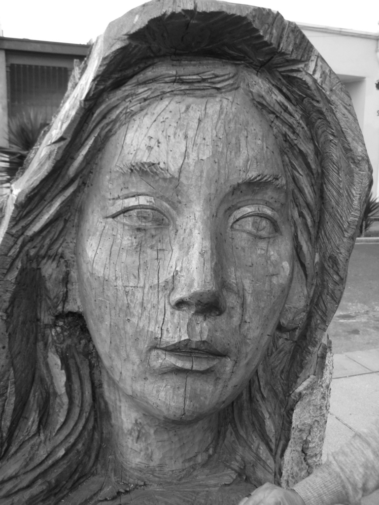 Woman face carved out of a tree trunk