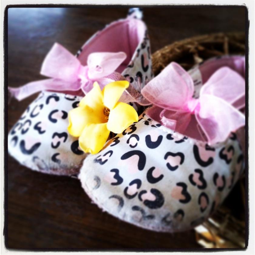 Baby shoes cradling a puakinekine flower